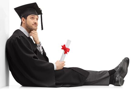 Pensive graduate male student holding a diploma sitting on the floor and leaning on a wall isolated on white background