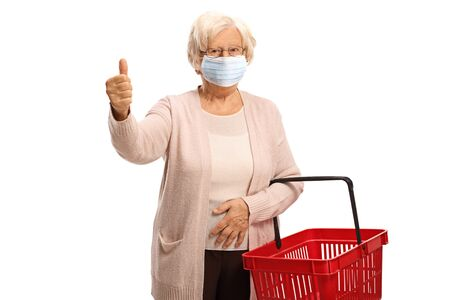 Elderly woman wearing a face medical mask showing a thumb up sign and holding a shopping basket isolated on white background