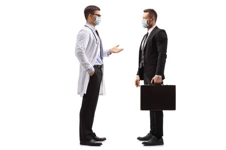 Full length profile shot of a doctor and businessman with medical face masks standing and talking isolated on white background