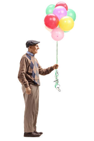 Full length profile shot of a senior man holding a bunch of colorful helium balloons isolated on white background