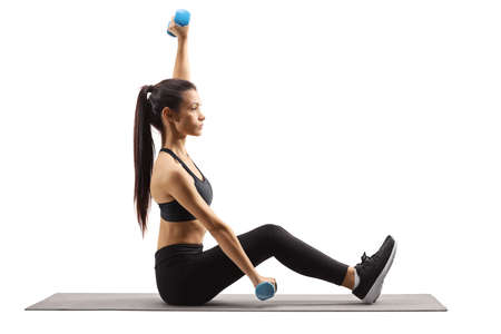 Young woman exercising with dumbbells on a mat isolated on white background