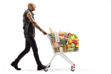 Full length profile shot of a bald punk walking with a shopping cart full of food isolated on white background