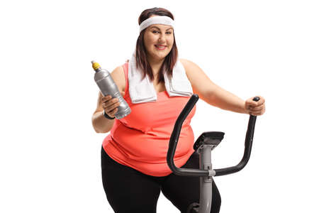 Chubby young woman on a stationary bike holding a plastic bottle isolated on white background Imagens