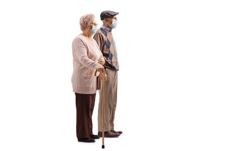 Full length profile shot of a senior couple with walking cane wearing medical face masks isolated on white background Imagens