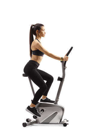 Profile shot of a young woman riding a stationary bike isolated on white background