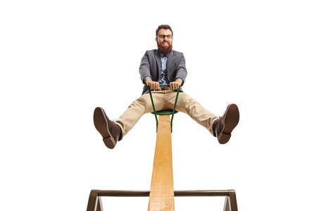 Cheerful positive bearded man riding on a seesaw with legs up isolated on white background