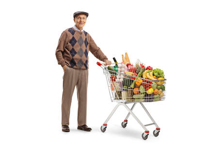 Full length portrait of a senior gentleman standing with a shopping cart full of food isolated on white background