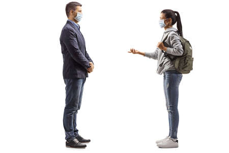 Full length profile shot of a female student and a young man with medical face masks having a conversation isolated on white background