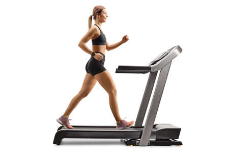 Full length profile shot of a muscular young woman running on a treadmill isolated on white background Imagens