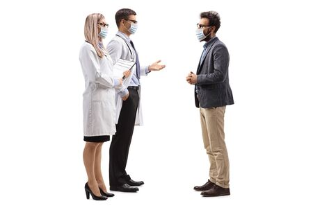 Full length profile shot of male and female doctors wearing protective medical masks and talking to a man with a medical face mask isolated on white background Foto de archivo