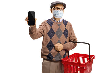 Elderly man with a medical face mask showing a mobile phone and carrying a shopping basket isolated on white background Imagens