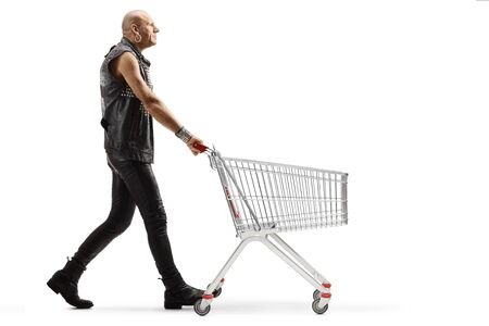 Full length profile shot of a punk man in leather clothes pushing an empty shopping cart isolated on white background