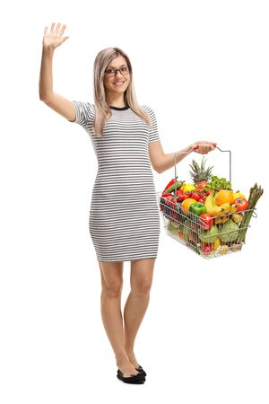 Full length portrait of a young woman with a shopping basket with fruits and vegetables waving isolated on white background