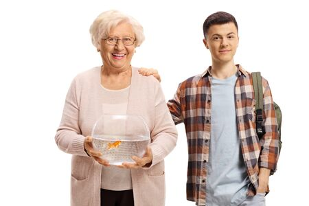Senior woman holding a bowl with a goldfish and standing next to a male student isolated on white background