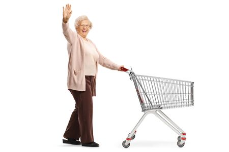 Full length shot of a senior lady waving and pushing an empty shopping cart isolated on white background