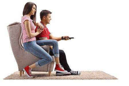Young female and male sitting in an armchair and holding a remote control isolated on white background