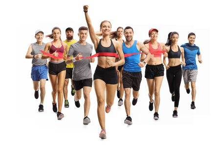 Full length portrait shot of people running a marathon race and a young woman finishing first isolated on white background Stock Photo