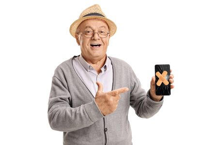 Elderly man holding a mobile phone with plasters on the broken screen isolated on white background