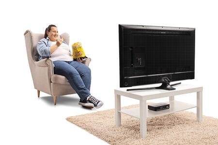 Overweight woman watching tv and eating tortilla chips isolated on white background Banco de Imagens