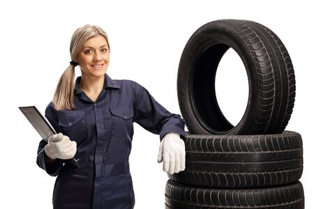 Female auto mechanic leaning on tires isolated on white background