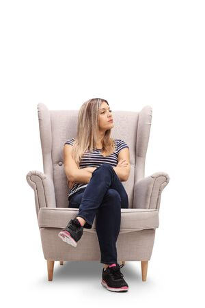 Angry young woman sitting in armchair and looking to the side isolated on white background