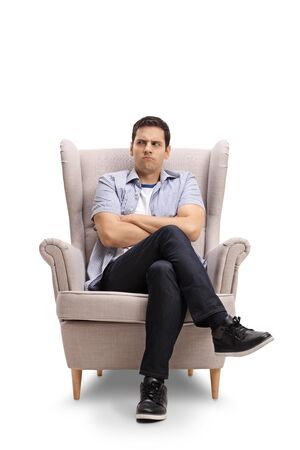 Angry young man making a grimace and sitting in armchair isolated on white background