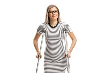 Young woman with crutches isolated on white background