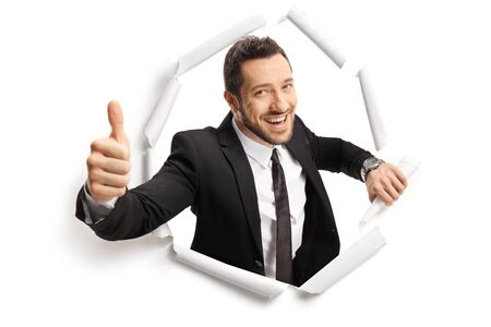 Businessman peeking through a paper hole and showing a thumb up isolated on white background