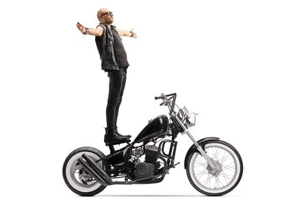 Bald punk daredevil man standing on a chopper motorbike isolated on white background