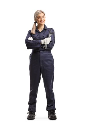 Full length portrait of a female worker in a uniform holding a wrench isolated on white background