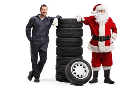 Auto mechanic and Santa Claus posing with a pile of tires isolated on white background