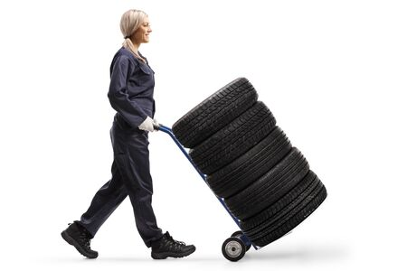 Full length profile shot of a female auto mechanic walking and pushing tires on a hand-truck isolated on white background