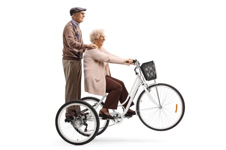 Senior woman riding a tricycle and a senior man behind her isolated on white background Standard-Bild