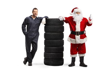Full length portrait of an auto mechanic and Santa gesturing thumb up and leaning on a pile of tires isolated on white background Stock Photo