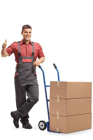 Travailleur en uniforme debout à côté d'un camion à main chargé de boîtes et montrant les pouces vers le haut isolé sur fond blanc