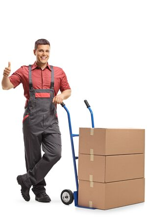 Worker in a uniform standing next to a hand truck loaded with boxes and showing thumbs up isolated on white background