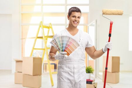 House painter with a color swatch and a paint roller inside a house Standard-Bild