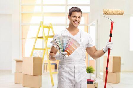Peintre en bâtiment avec un échantillon de couleur et un rouleau à peinture à l'intérieur d'une maison Banque d'images