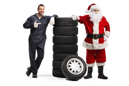 Auto mechanic pointing at a pile of tires and posing with Santa Claus isolated on white background