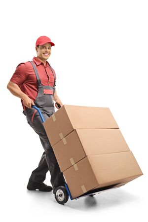 Male worker pushing a hand truck loaded with boxes isolated on white background