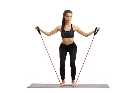 Full length portrait of a slim young female exercising with a resistance band isolated on white background Stock Photo
