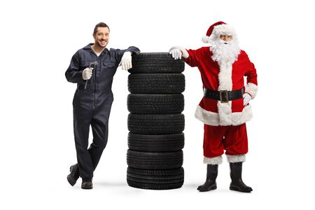 Auto mechanic holding a wrench and Santa Claus posing with a pile of tires isolated on white background