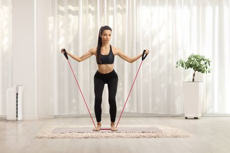 Full length portrait of a slim young female exercising with a stretching band at home