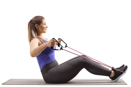 Woman sitting on the floor and exercising with a resistance band isolated on white background