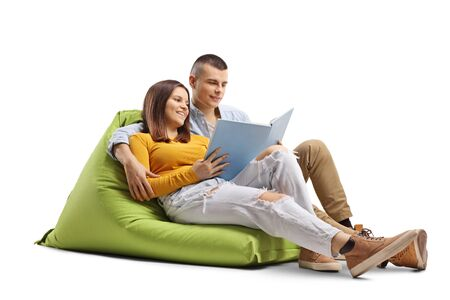Young male and female students sitting on a beanbag and reading a book isolated on white background Standard-Bild