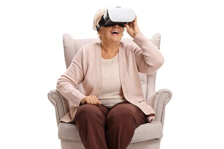 Senior woman sitting in an armchair and using a VR headseat isolated on white background