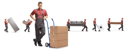Male worker with boxes on a hand-truck and other carrying furniture isolated on white background Foto de archivo