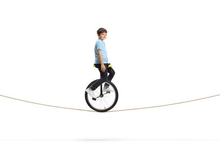 Full length shot of a boy riding a unicycle on a rope and looking at the camera isolated on white background