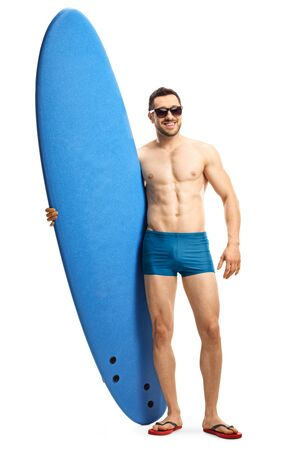 Full length portrait of a young guy in swimwear wearing sunglasses and posing with a surfing board isolated on white background