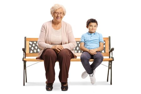 Senior woman sitting on a bench with her grandson isolated on white background
